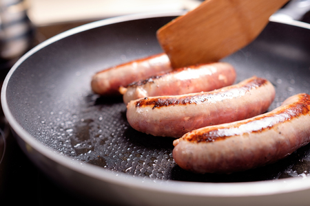 Cooking sausages in the dripping pan with oil Foto de archivo