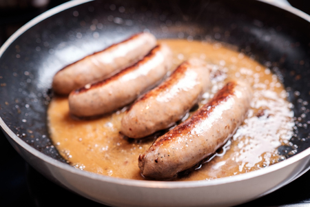 dripping pan: Cooking sausages in the dripping pan with oil Stock Photo