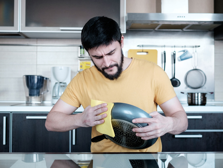 dripping pan: Attractive caucasian man cleaning the dripping pan in the kitchen Stock Photo