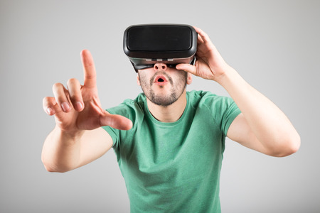 Man with virtual reality glasses showing gesture isolated on a gray background