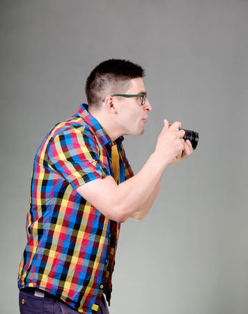 suddenness: Handsome man dressed in a multicolored shirt with photo camera standing isolated on gray background