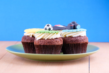 celebration smiley: Delicious cupcakes with icons of ball, tuxedo, smiley and camera on it with green plate on wooden desk and blue background Stock Photo
