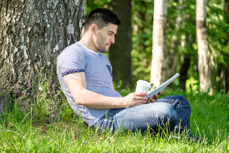 Young man sitting on a grass in the park, reading a book and drinking coffee