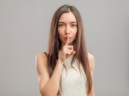 Young woman making keep it quiet gesture against a gray background Stock Photo