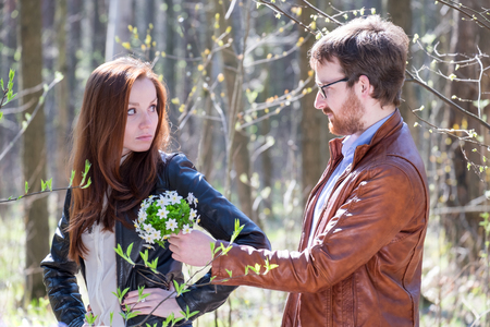 Young lovely couple with bouquet of spring flowers in park