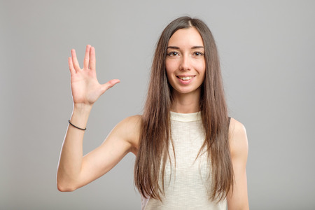 Pretty woman making Vulcan greeting isolated on gray Stock Photo