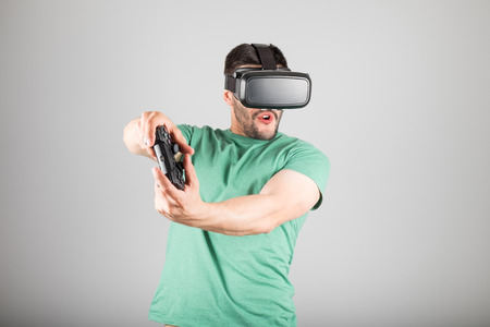 Young man playing with virtual reality glasses and video game controller isolated on a gray background