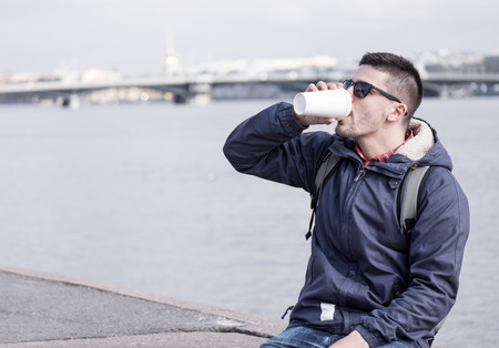 Portrait of young attractive man with coffee cup sitting on promenade and city sight seeings as background