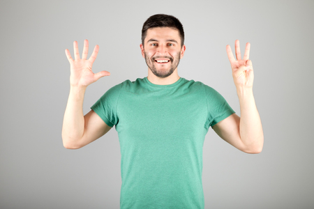 numerate: Handsome man counting to eight isolated on a gray background