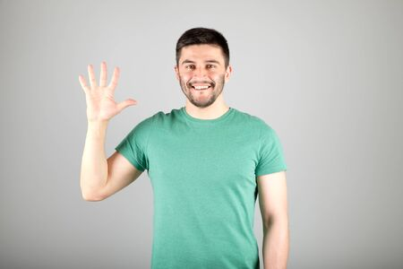 Handsome man counting to five isolated on a gray background