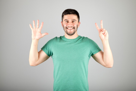 numerate: Handsome man counting to seven isolated on a gray background