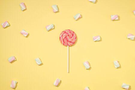 Sweet marshmallows minimalism set with red lollipop on pastel straw yellow background Stock Photo