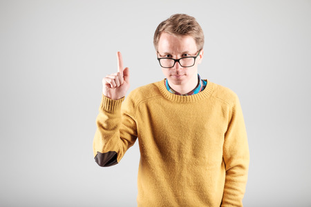 Serious young man points his forefinger up isolated on gray background Stock Photo