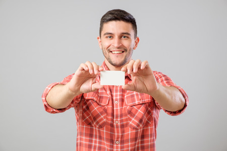 Young man holding and showing blank business card isolated on gray background