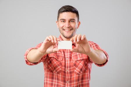 Hombre joven que sostiene y que muestra la tarjeta de visita en blanco aislado en fondo gris Foto de archivo - 67873544