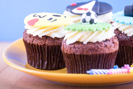 cup four: Delicious cupcakes with icons of ball, tuxedo, smiley and camera on it with yellow plate and three candles on wooden desk and blue background