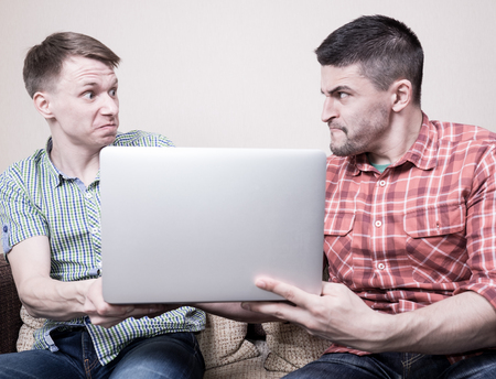 conflicting: Two young angry guys conflicting for laptop computer Stock Photo