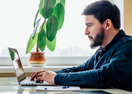 Busy handsome businessman in home office working on his laptop