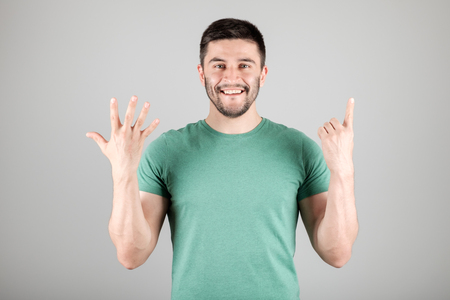 numerate: Handsome man counting to six isolated on a gray background