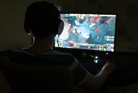 Hombre joven excitado con los auriculares que juegan los juegos de ordenador en una habitación oscura Foto de archivo - 65710761