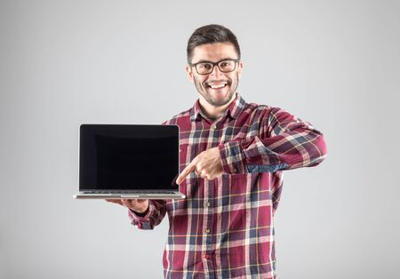 Smiling hipster pointing finger on blank laptop screen over gray background66 Stock Photo
