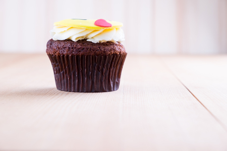 Delicious cupcake with smiley icon on it on wooden desk Stock Photo
