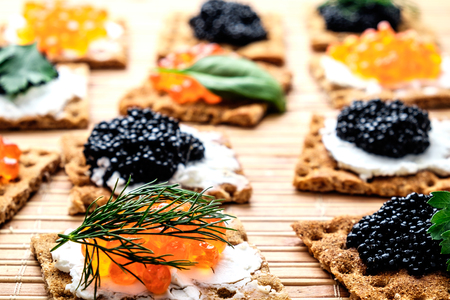 Group of snacks with red and black caviar