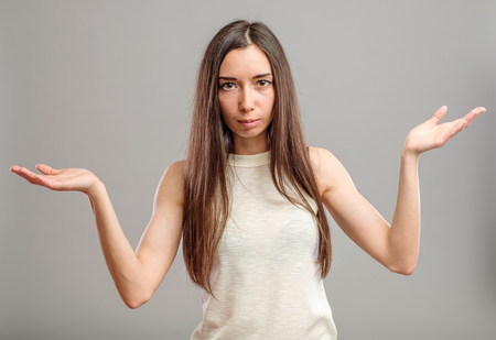 Attractive woman holding her hands out saying that she does not know isolated over gray background