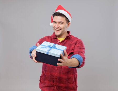 Handsome guy holding a gift and emotionally happy Christmas isolated on gray background