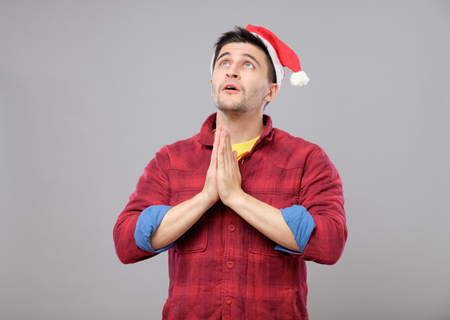Young man in Santa hat praying isolated on gray background Stock Photo