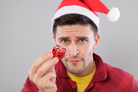 Closeup portrait unhappy, upset man holding small red box gift, disgust on face, isolated on gray background. Negative human emotion, facial expression