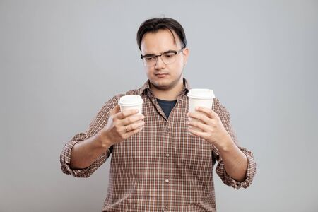 choise: Portrait of a man choosing a cup of coffee isolated on a gray background