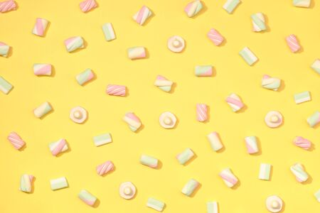 paletas de caramelo: malvaviscos minimalismo dulce fijado en la paja pastel de fondo de color amarillo