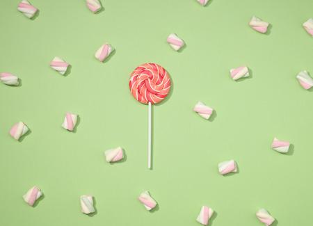paletas de caramelo: malvaviscos dulces minimalismo establecen con piruleta roja en fondo verde en colores pastel de manzana