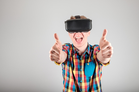 Man with virtual reality glasses showing thumb up isolated on a gray background Stock Photo
