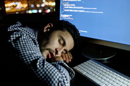 deprived: Freelancer programmer falling his face down taking a nap with computer. Concept of tired and lazy Stock Photo