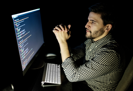 job deadline: Software developer computer at dark home office. Startup and hard working concept