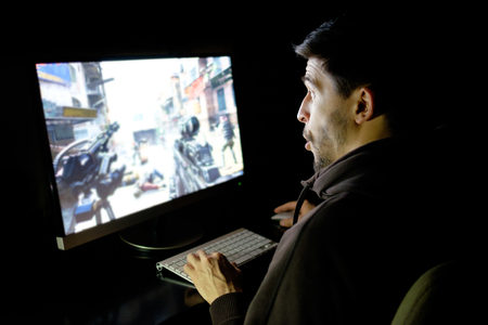 Amazed guy emotional playing computer game online in dark room