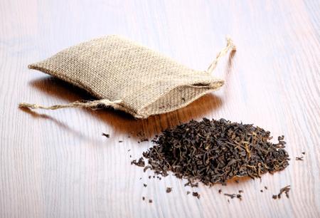 Dry black Indian tea with vintage burlap bag on wooden background
