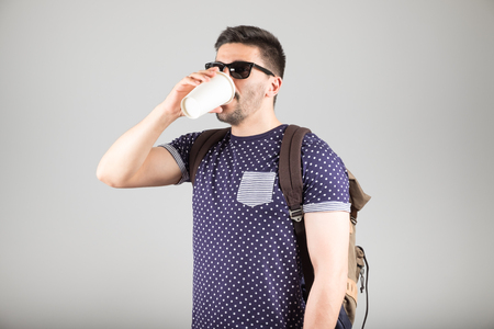 Smiling man with backpack drinking coffee isolated on gray background Stock Photo
