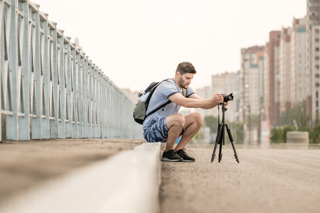 Man with photo camera on tripod taking timelapse photos in the city Stock Photo