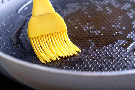 greasing: Greasing dripping pan by yellow silicone brush with olive oil