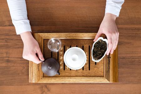 Junge Frau Durchführung von Tee-Zeremonie mit chinesischen Tee-Set