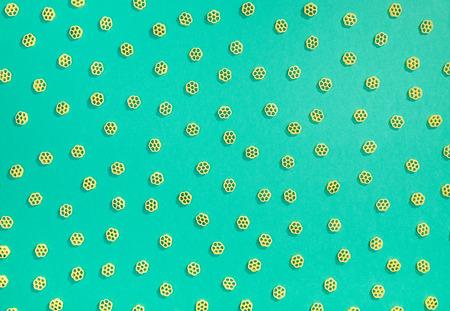 Rotelle pasta random flat lay pattern on green background