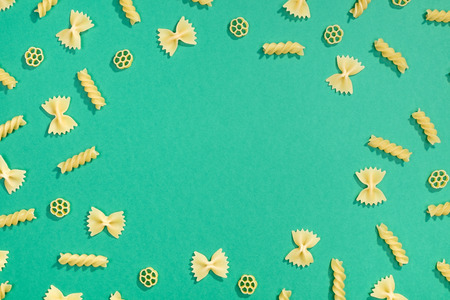 Frame from wheat pasta on green background. Random pattern. Flat lay Stock Photo