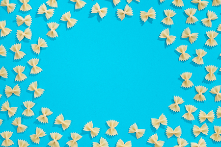 Frame from wheat pasta on blue background. Random pattern. Flat lay
