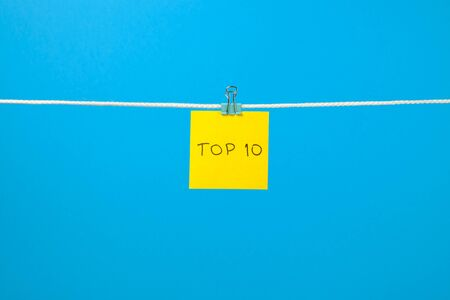 string top: Yellow paper sheet on the string with text �Top 10� over colorful background Stock Photo