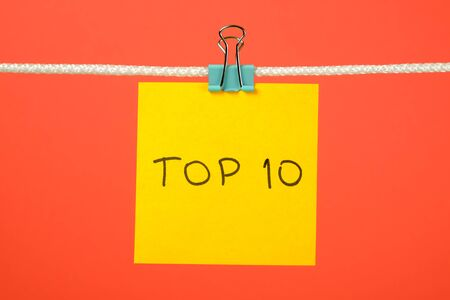 """string top: Yellow paper sheet on the string with text """"Top 10"""" over colorful background"""