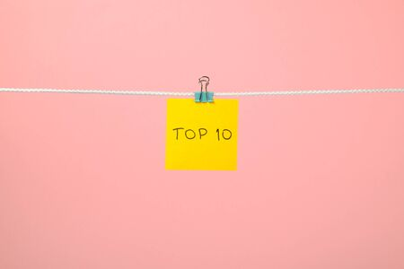 string top: Yellow paper sheet on the string with text Top 10 over colorful background