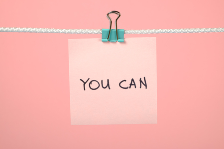 tu puedes: Pink paper sheet on the string with text You Can over colorful background